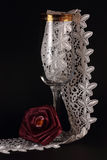 Red silk rose and glass. Red  silk rose,tall glass with gold and white laces on a black background Stock Image