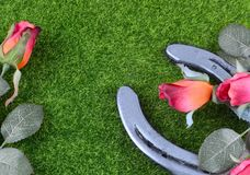 Red silk roses, a horseshoe and artificial green grass for the running of the thoroughbred race called the Kentucky Derby. Copy space royalty free stock photography