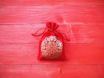 Red silky money bag with string on wood background Stock Photography
