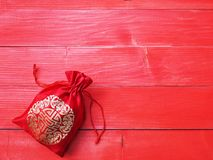 Red silky money bag with string on wood background Royalty Free Stock Photos