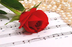 Red silky rose and pearls. Red silky rose with musical notes Stock Photo