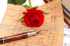 Red silky rose with a pen Royalty Free Stock Photography