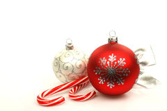 Red and silver christmas ball and two christmas ca. Ndy canes isolated on a white background Royalty Free Stock Photos