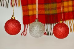 Red and silver Christmas balls against a woolen red and yellow checkered scarf with a fringe. Concept of holidays, Christmas and N. Ew Year, close up stock photos
