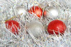 Red and silver Christmas balls and shiny tinsel of silver color, background and concept of holidays, Christmas and New Year. Close up royalty free stock images
