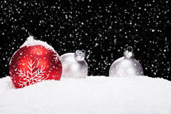 Red and silver christmas balls in snow. On black background while snowing stock photography