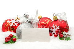 Red,silver christmas decoration on snow with white wishes card Royalty Free Stock Photos
