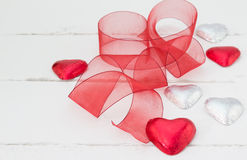 Red and silver foil covered heart Valentine chocolates on white. Image of red and silver foil covered heart Valentine chocolates on white rustic wood backround Royalty Free Stock Image