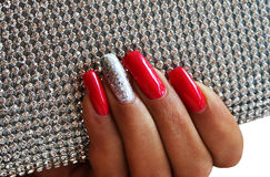 Red and silver  manicure. Red and silver shiny manicure on background Stock Photography