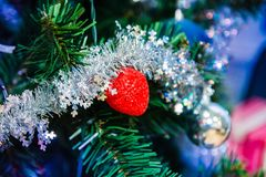 Red and silver toy and a silver garland on a Christmas tree. Close up stock image