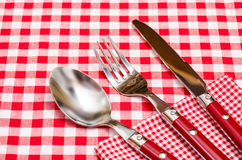Red silverware on a red checkered napkin Royalty Free Stock Photos