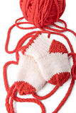 Red skein and knitted socks Stock Photos