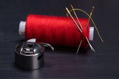 Red skein of thread at the needle and the Shuttle hook for sewing machine, on a dark background royalty free stock photos