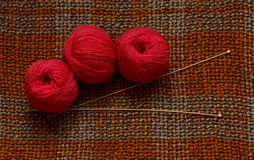 Red skeins, wooden knitting needles on a brown knitted fabric. Red yarn skeins and wooden knitting needles are on a brown knitted fabric. Top view Stock Image