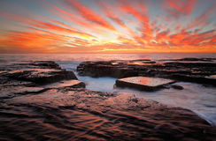 Red skies over North Narrabeen Australia. Red sunrise skies over the ocean and eroded rock channel and reclections on the dark wet rocks.  Location North Stock Image