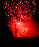Red sky fireworks. Red fireworks silhouteeting the crowd Royalty Free Stock Image