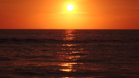 Red sky horizon hung over the water space at sunset. Red sky horizon with the round sun middle hung over the water space at sunset stock footage