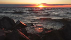 Red sky over a rocky seashore. Sunset landscape. stock footage
