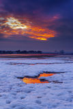 Red sky sunset over snowy Poole beach Royalty Free Stock Photography