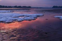 Red sky sunset over snowy Poole beach Royalty Free Stock Images