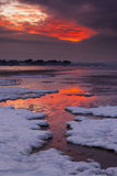 Red sky sunset over snowy Poole beach Royalty Free Stock Photos