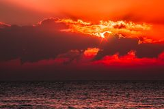 Red sky tropical sunset. Beautiful fantasy cloudscape with blood. Orange light from sun behind cloud. Lens flare stars add to the spiritual nature of the serene Royalty Free Stock Photography