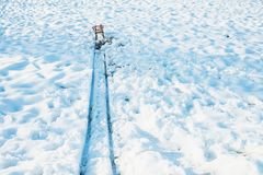 Red sled at the end of track in snow. Red sled at the end of a track in snow stock photography