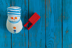 Red sled and handmade snowman on blue wooden Royalty Free Stock Images