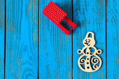 Red sled and handmade snowman on blue wooden Stock Photos