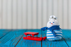 Red sled and little handmade snowman on light Stock Photos