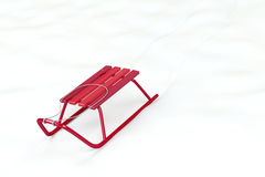Red sledge. Metal red sledge in the snow Royalty Free Stock Photos