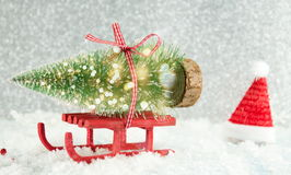 Red sleigh carrying a small Christmas tree Stock Image