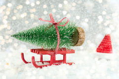 Red sleigh carrying a small Christmas tree Royalty Free Stock Images