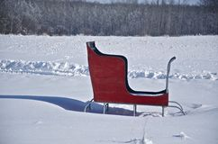 Red sleigh on a field of fresh snow. A red, wooden sled brightens up a field of freshly fallen snow Stock Photos