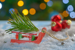 Red sleigh toy and Christmas tree. On fake snow Stock Photo
