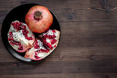 Red sliced pomegranate on plate on wooden background top view mock up Stock Photos