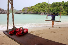 Red Slipper on the wooden cradle on the beach. Red Slipper on the wooden cradle on the beach with people activety background on the island in Thailand Stock Images