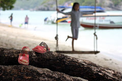 Red Slipper on the wooden cradle on the beach. Red Slipper on the wooden cradle on the beach with people activety background on the island in Thailand stock photo