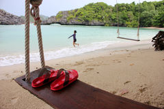 Red Slipper on the wooden cradle on the beach. Red Slipper on the wooden cradle on the beach with people activety background on the island in Thailand Royalty Free Stock Image
