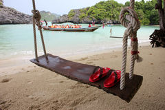Red Slipper on the wooden cradle on the beach. Red Slipper on the wooden cradle on the beach with people activety background on the island in Thailand Stock Photography