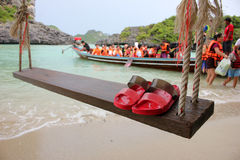 Red Slipper on the wooden cradle on the beach. Red Slipper on the wooden cradle on the beach with people activety background on the island in Thailand Royalty Free Stock Images