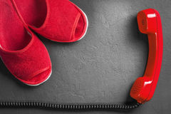 Red slippers with handset on the floor royalty free stock photo