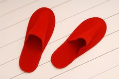 Red slippers from hotel, red slippers from airplane is on white. Red slippers from hotel, red slippers from airplane are on white wooden floor, home slippers are Stock Image