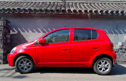 Red small car and wall Royalty Free Stock Photos