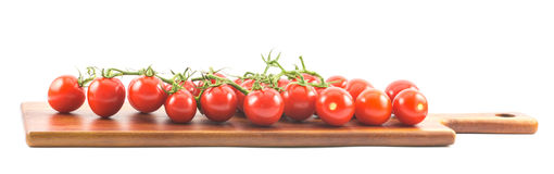 Red small cherry tomatoes on a wooden surface and white background.  royalty free stock photos