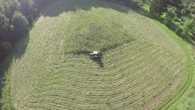 Red small old tractor mowing grass from meadow in farmland, aerial view stock video