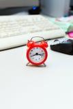 Red Small Retro Alarm Clock on white desk Stock Images