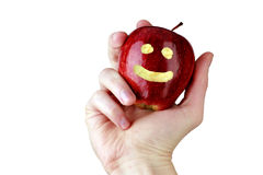 Red smiling apple, optimistic vitamin diet. Red apple with smile held in male hand. Optimistic weight loss. An apple a day concept Stock Image