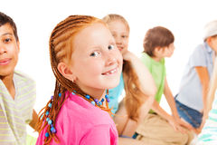 Red smiling girl turning back with her friends Royalty Free Stock Photos