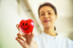 Red smiling heart held by smiling female nurse`s hand, representing giving effort high quality service mind to patient. Stock Images